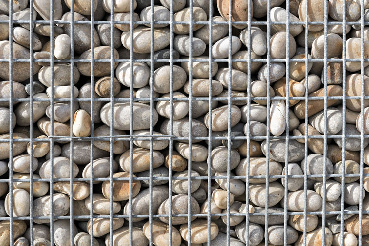 Gabion with Pebbles Backgrounds Textured  Close-up Full Frame Abstract Concept Conceptual Safety Protection Contrasts Gabion Pebble Pebbles Forms Lines Rounded Texture Textured  Background Container Division Mesh Grid Shape