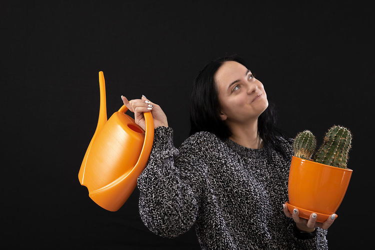 Portrait of young woman holding drink against black background
