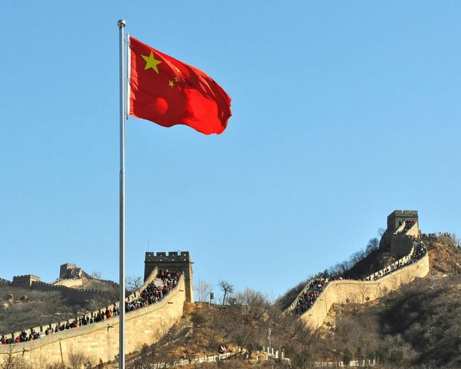 People at great wall of china by chinese flag against clear sky