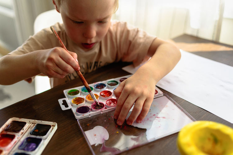 High angle view of boy with watercolor paints on table