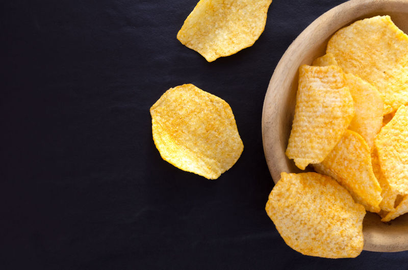 Potato chips on table background.