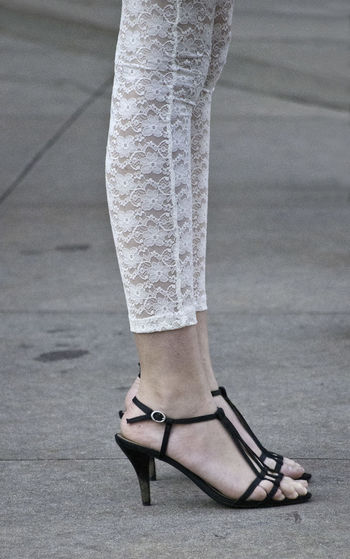 Low section of woman in high heels standing on street