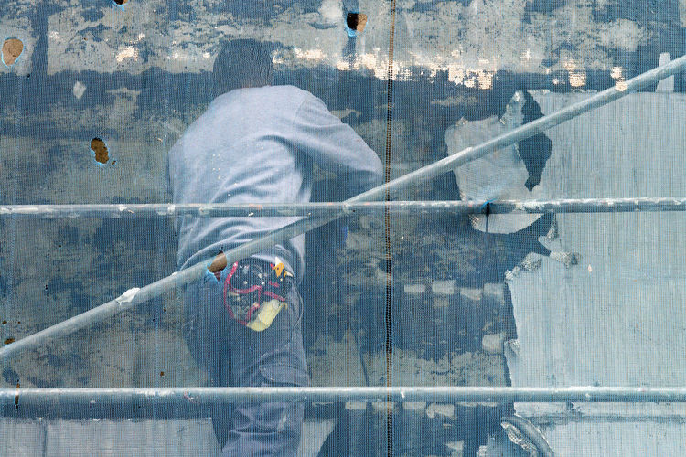 roll felt uninstalling in building facade by unrecognizable construction workers in scaffolding Construction Construction Site Construction Machinery Scaffolding Unrecognizable People Worker Workers Building Exterior Building Facade Building Maintenance Building Restoration Buillding Repair Construction Industry Construction Worker Felt Protection Safety Site Unrecognizable Person