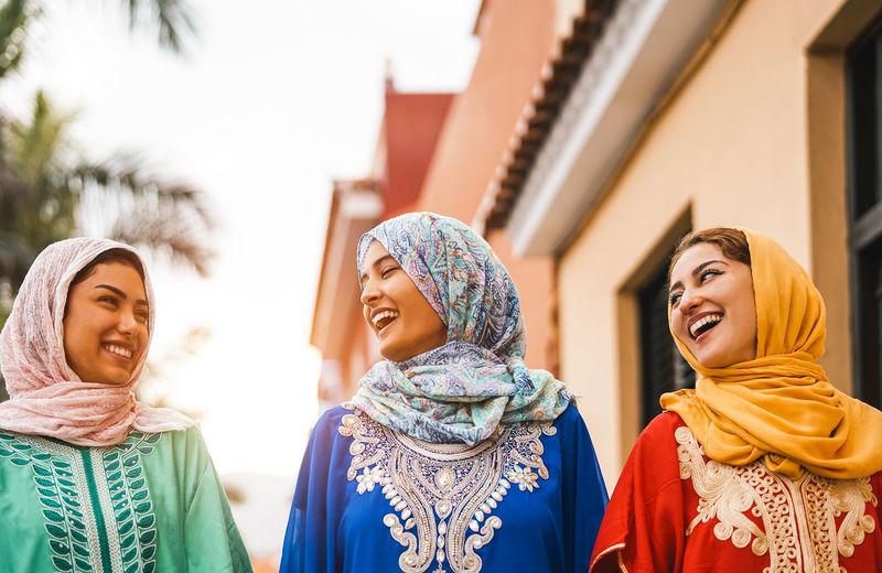 Happy female friends walking by building
