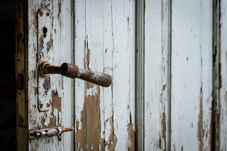 Selective focus photography. Old wooden door with damaged paint. Abandoned Close-up Closed Damaged Day Decline Deterioration Door Entrance Latch Lock Metal Nail No People Old Outdoors Protection Ruined Run-down Rusty Safety Security Weathered Wood - Material