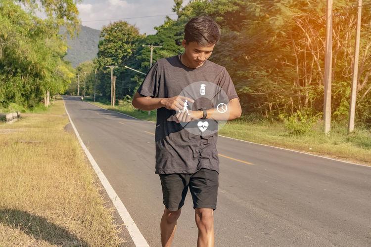 Full length portrait of man standing on road