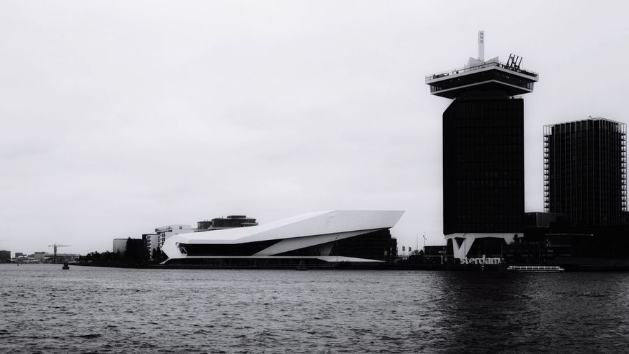 Amsterdam always has an angle. Architecture Building Exterior Water Sky Outdoors Travel Destinations Travel Built Structure Waterfront City Modern Black And White Collection  Black And White Photography Blackandwhite Amsterdam Amsterdamcity Design