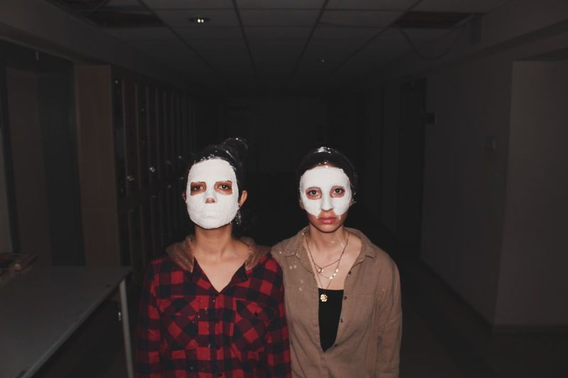 Portrait of friends with facial mask standing in passage
