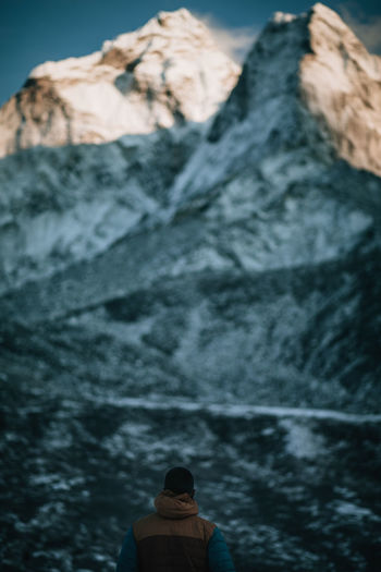 Rear View Of Man Against Rocky Mountains During Winter