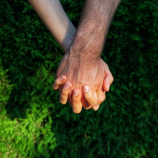Low section of unrecognizable couple holding hands on grass