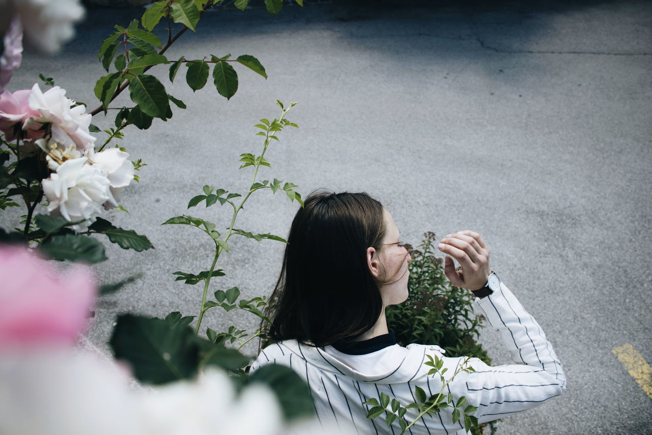 High Angle View Of Young Woman By Plants At Road