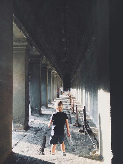 Full length of boy standing in corridor