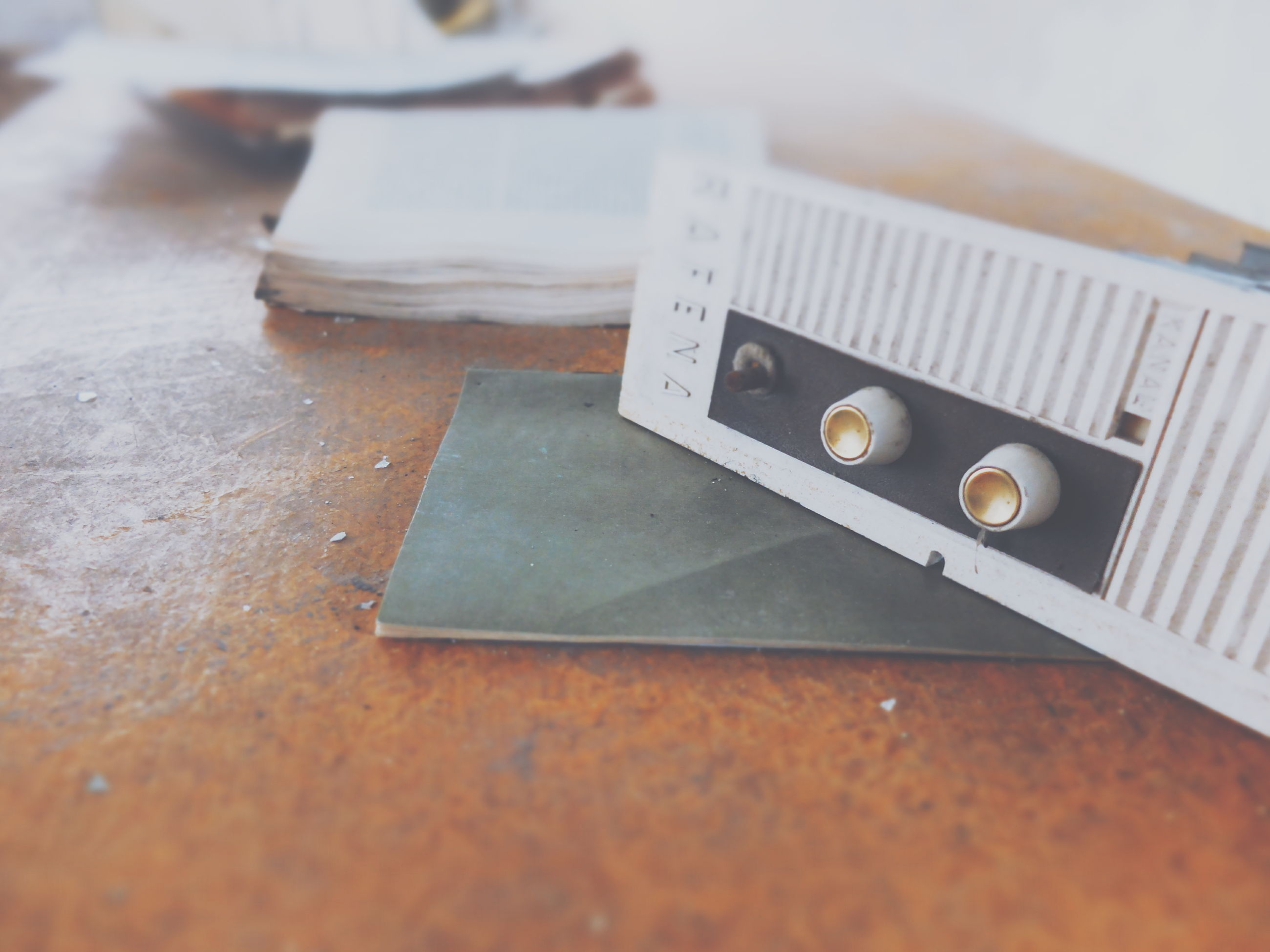 close-up, indoors, still life, selective focus, table, high angle view, metal, wood - material, no people, focus on foreground, communication, old, metallic, day, technology, equipment, retro styled, single object, old-fashioned, number