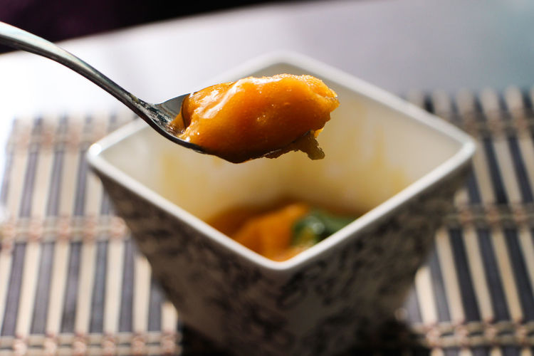 Close-up of mango sorbet on spoon above bowl
