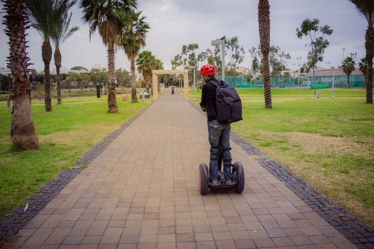 Day Full Length Grass Headwear Helmet Lifestyles Nature One Person Outdoors People Real People Rear View Riding Segway Sky The Way Forward Transportation Tree