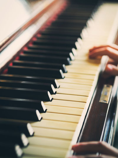 Close-up of hands playing piano in home