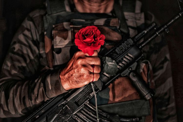 Midsection of man holding red roses