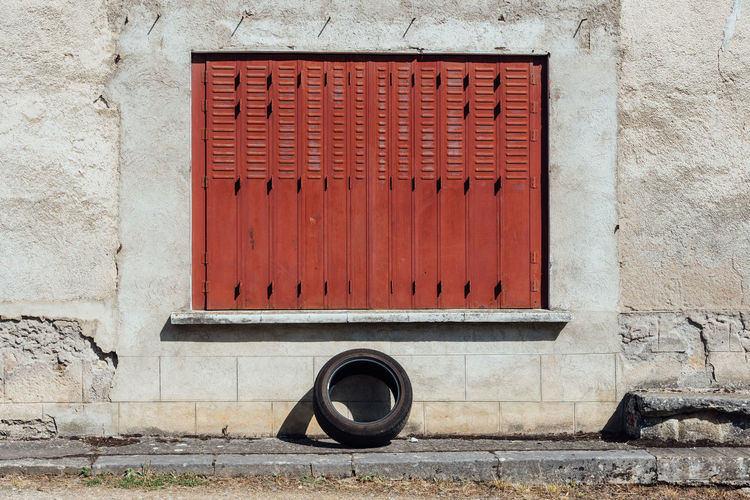 Tyre Abandoned Tire Wheel Window Closed Window  Wall - Building Feature Exterior EyeEm Selects Close-up Architecture Built Structure Building Exterior Deterioration Obsolete Discarded Bad Condition Rusty Damaged Peeling Off Run-down Weathered Shutter Locked Worn Out Closed Corrugated Iron Corrugated Peeled The Street Photographer - 2018 EyeEm Awards