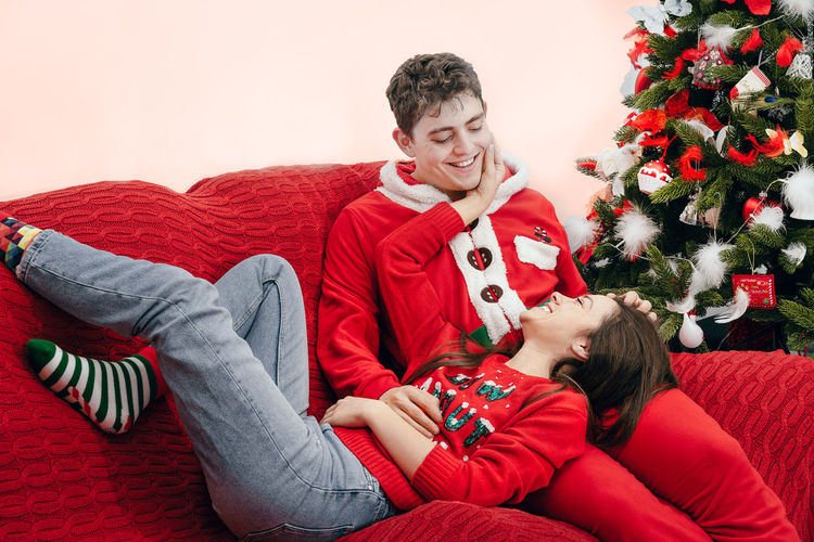 The last one. Couch Indoors  Christmas Clothing Holiday Smiling One Woman Only One Man Only Young Adult Young Couple Couple - Relationship People Real People Interior Home Interior Red Living Room Sitting Human Hand Men Christmas Portrait Domestic Life Bed Knitting Bauble Christmas Decoration Christmas Ornament christmas tree Decorating The Christmas Tree Christmas Bauble