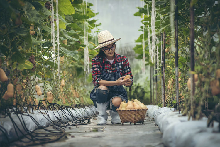 Full length of smiling man sitting by basket against plants