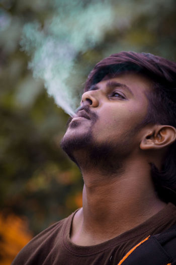 Portrait of young man smoking outdoors