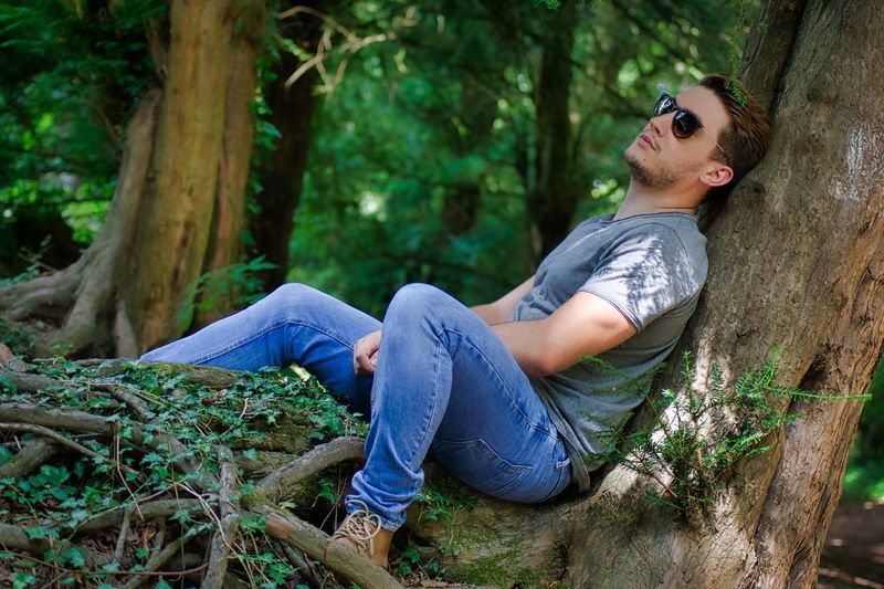 Side view of man sitting on tree trunk in forest