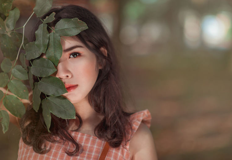 Close-up of young woman with plant