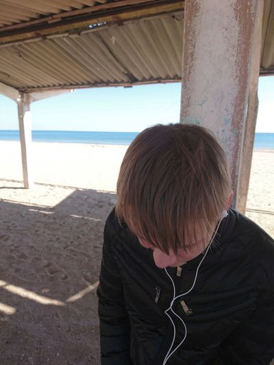 Rear view of boy on shore at beach