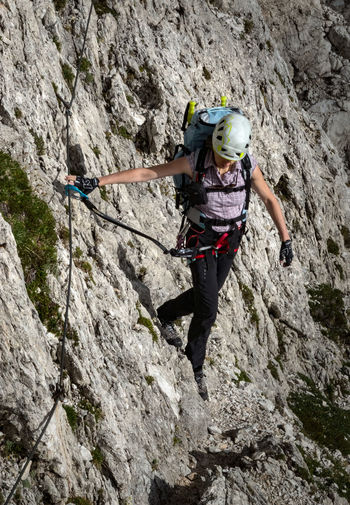 High angle view of woman climbing on mountain against sky