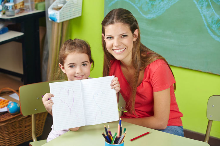 Portrait of smiling girl showing drawing at classroom