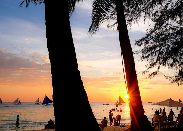 Holiday Philippines Relaxing Beach Beauty In Nature Boracay Cloud - Sky Crowd Group Of People Horizon Over Water Land Large Group Of People Men Nature Orange Color Outdoors Real People Scenics - Nature Sea Silhouette Sky Sun Sunset Tree Water