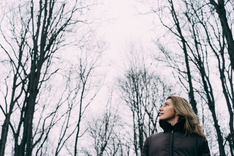 Winter One Woman Only Bare Tree Only Women One Person Cold Temperature Adults Only Adult Tree Forest Warm Clothing People Nature Headshot Leisure Activity Be. Ready. Portrait Human Body Part Outdoors Standing Shades Of Winter