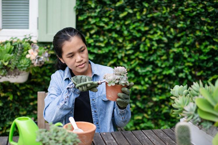 Young woman gardening in backyard