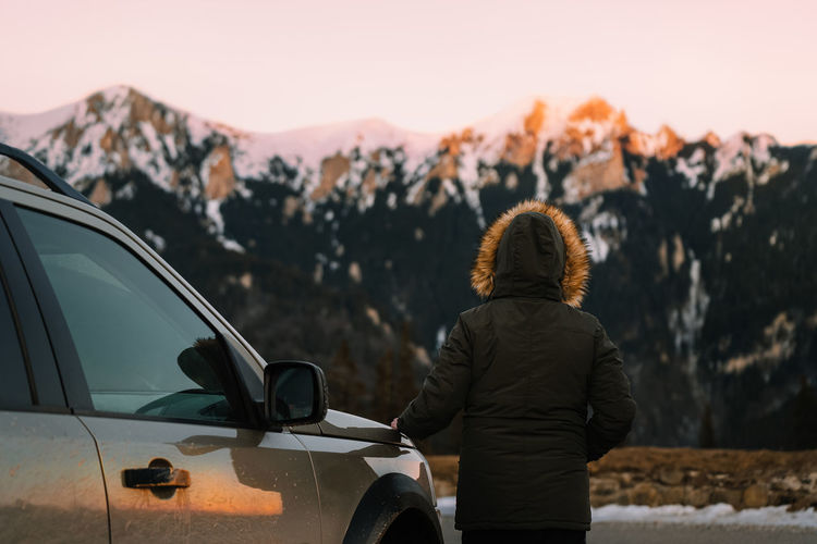 Rear view of man standing by car against mountains at sunset
