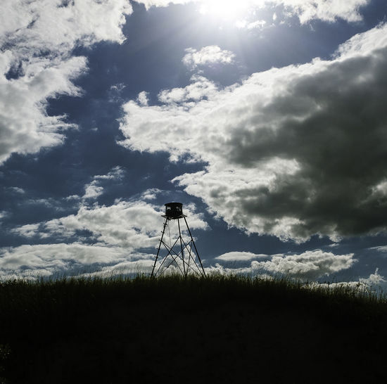 Silhouette of windmill on field against sky