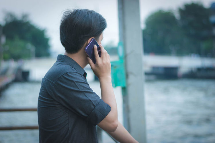 Man talking on mobile phone against pond