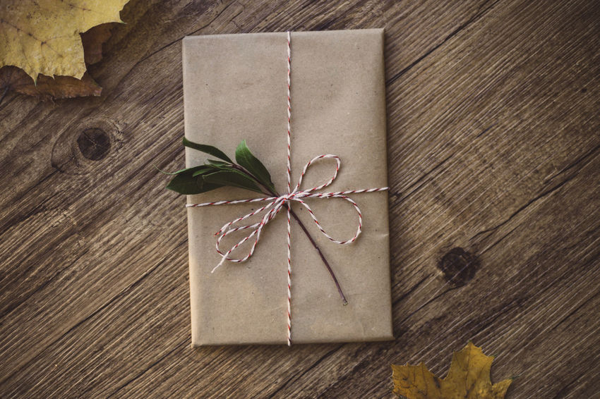 Wrapped gifts on wooden table Rustic Present Christmas Holiday Love Wrap Chritsmas Decoration Gift Paper Wrapped Box - Container Indoors  No People Close-up High Angle View Leaf Brown Directly Above Ribbon - Sewing Item Wood - Material Tied Up Fragility Table Day