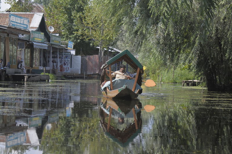 A local people in kashmir using a boat to travel Tree Water Reflection Plant Nature Waterfront Day Architecture Lake Two People Built Structure Adult Full Length Men Transportation Real People People Nautical Vessel Mode Of Transportation Outdoors