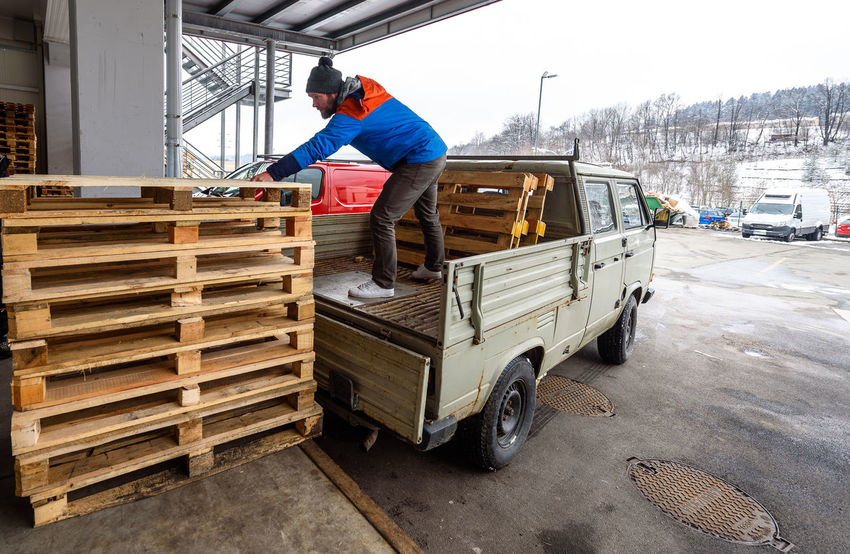Man is loading wooden pallets on a truck in winter. Stacking wooden euro pallets on a truck lorry container for shipping and transport. Container Delivery Delivery Service Euro Pallet Industry Lorry Traffic Transport Transportation Winter Bunch Cold Day Loading Men One Person Pallete Real People Shipping  Stacking Truck Trucker Van Wooden Working