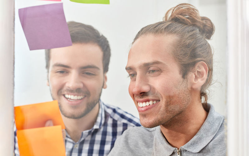 Smiling businessmen sticking adhesive notes on glass at office