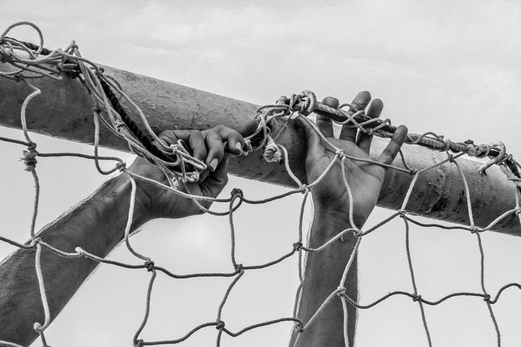 Cropped image of man attaching net on goal post against sky