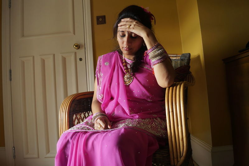Woman With Headache Sitting In Pink Sari On Chair At Home