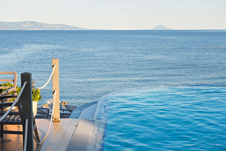 Empty azul infinity pool on the sunset, quiet blue sea Infinity Pool Absence Beauty In Nature Blue Chair Day Empty Horizon Horizon Over Water Nature Nautical Vessel No People Outdoors Scenics - Nature Sea Seat Sky Sunlight Swimming Pool Tranquil Scene Tranquility Water