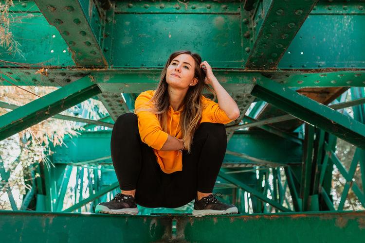 Portrait of woman sitting on bridge