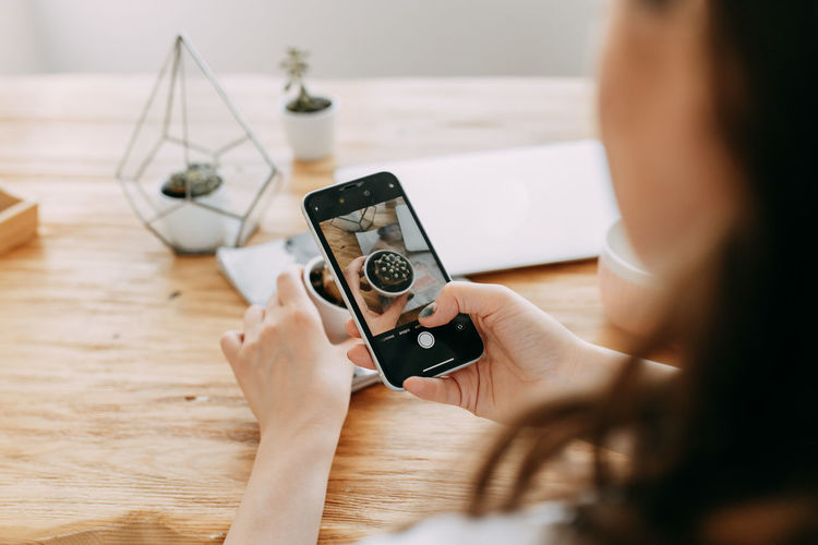 A young woman takes photos of objects goods things using a mobile phone creates content for a blog