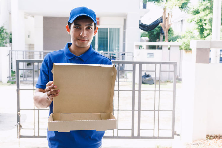 Portrait of salesman with empty cardboard box standing at gate way
