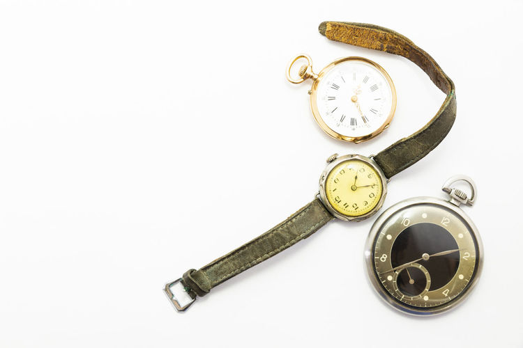High angle view of pocket watches and wristwatch against white background