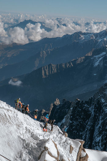 High angle view of people hiking on snowcapped mountain