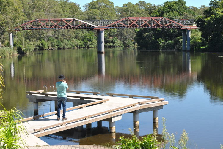 Rear view of man standing on bridge over lake