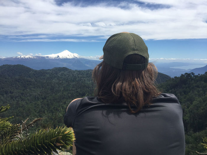 Rear view of person looking at mountains against sky